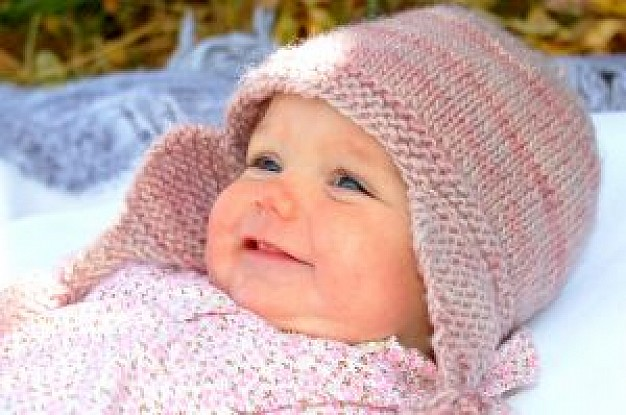 Photograph of a smiling baby girl with pink bonnet
